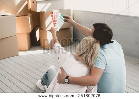 Man And Woman Sitting On Floor After Moving To New House Look At Palette Of Paints Choosing Right On
