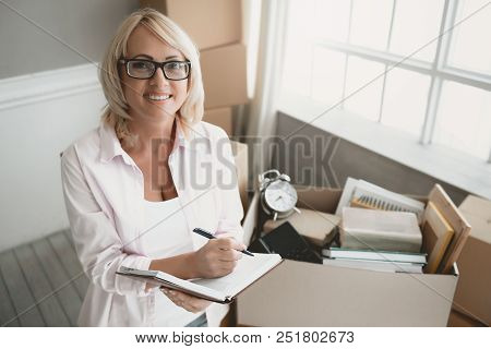 Smiling Blond Woman With Glasses With Notebook Makes List Of Things In Cardboard Box While Moving To