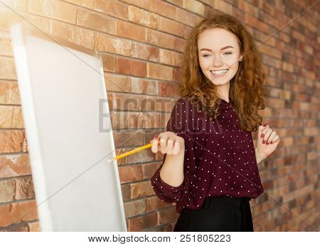 Learning Foreign Language. Cheerful Redhead Woman Teacher Near Whiteboard Explaining Rules, Copy Spa