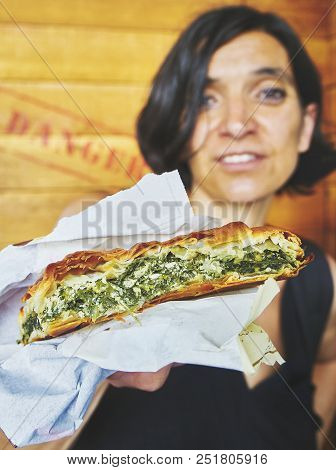 Greek Woman Eating A Traditional Spanakotiropita, Spinach And Feta Pie.