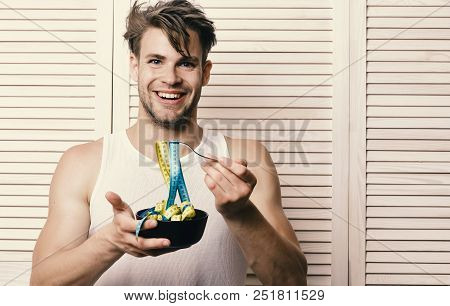 Fitness Lifestyle And Regime Idea. Man With Unshaven Face Holds Bowl And Fork With Measuring Tape. W
