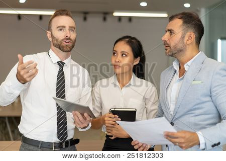 Serious Business People Standing And Discussing Issues In Office. Businesspeople Standing And Using