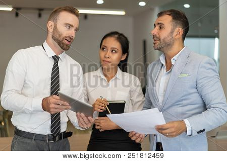 Serious Business People Working And Discussing Issues In Office. Businesspeople Standing And Using T