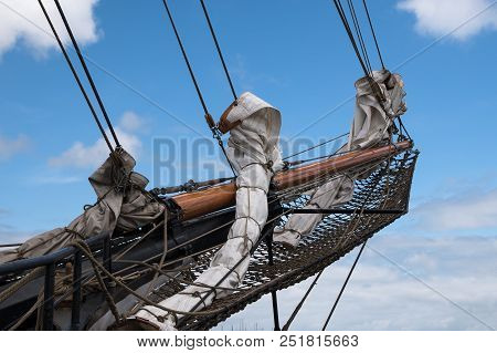 Bowsprit And Jib Boom With Reefed Sails On The Bow Of A Historic Sailing Ship Against A Blue Sky Wit