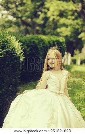 small girl kid with long blonde hair and pretty smiling happy face in prom princess white dress standing in garden with green grass sunny day outdoor. poster