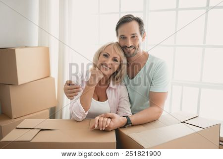 Happy Married Couple Stand By Window Of Apartment Putting His Hands On Cardboard Box In Front Of The