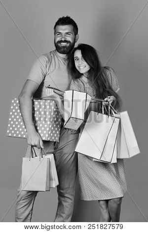 Man With Beard Holds Big Red Polka Dotted Box. Guy With Beard And Girl With Smiling Faces Do Shoppin