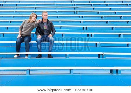 Woman pointing a man from empty sports tribune