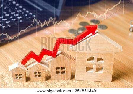A Red Arrow Above The Wooden Houses Up. Concept Of Increasing Demand And Supply In The Real Estate M