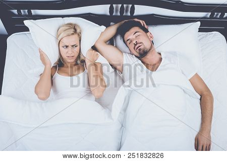 Top View Of Man Snoring Loudly Wife Blocks Ears. Snore Concept. Snore, Sleep, Apnea, Couple In Love,