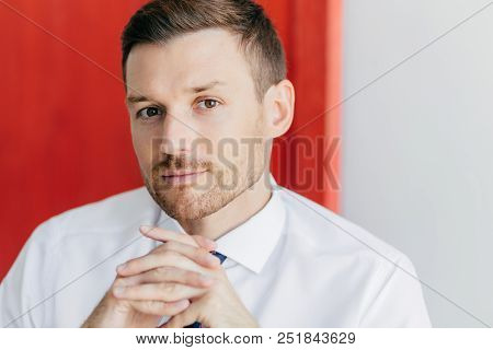 Cropped Image Of Confident Young Male Employee With Bristle, Keeps Hands Pressed Together, Dressed I
