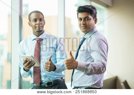 Cheerful Multi-ethnic Business Executives Showing Thumbs-up. Ambitious Successful Young Entrepreneur