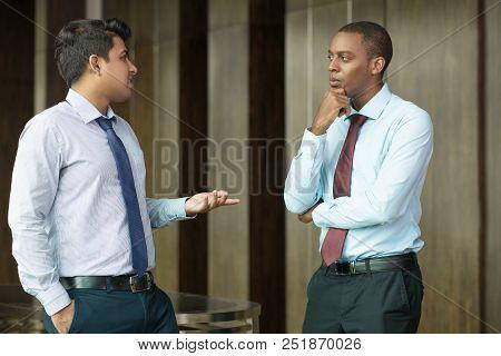 Pensive Entrepreneur Looking At His Talking Business Partner. Serious African-american Businessman L