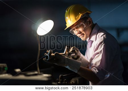 Mechanic Engineer Turner Miller verifies the accuracy of manufacturing steel parts with a scale the size of the measurement device. In the dark room with lamp background. poster