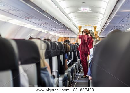 Stewardess In Red Uniform Giving Safety Instructions On Commercial Passengers Airplane. Unrecognizab