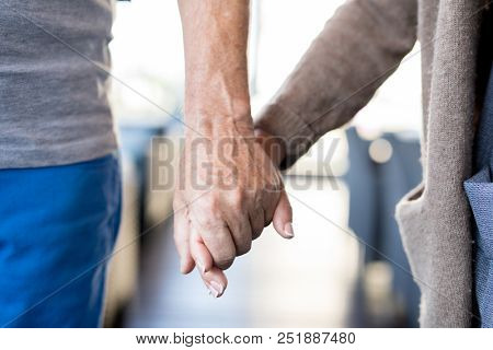 Close up of unrecognizable senior couple holding hands., symbol of love and longevity