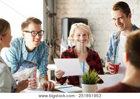Team of creative business professionals smiling cheerfully while discussing ideas  collaborating on startup project during meeting in modern office