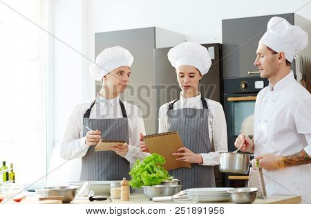 Pensive young students in chefs hats and aprons asking questions to chef with cooking pan while studying at master class