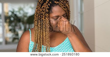 African american woman at home tired rubbing nose and eyes feeling fatigue and headache. Stress and frustration concept.