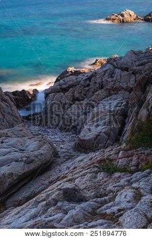 Rocky Coast With Foliage Towards Emerald Waters