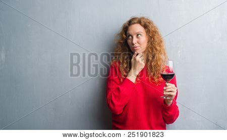 Young redhead woman over grey grunge wall drinking a glass of wine serious face thinking about question, very confused idea
