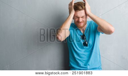 Young redhead man over grey grunge wall wearing casual outfit suffering from headache desperate and stressed because pain and migraine. Hands on head.