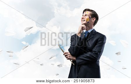 Portrait of confident and young business man holding paintbrush in his hand and looking away while standing against blue cloudy skyscape with flying paper planes on background. poster
