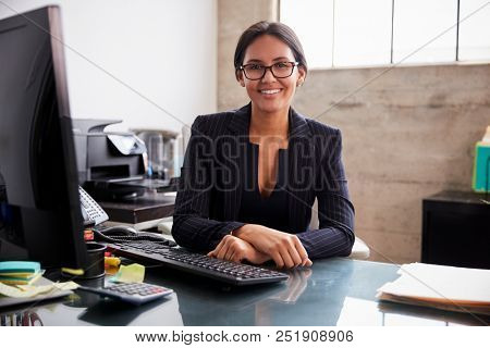 Young professional mixed race woman sitting in an office
