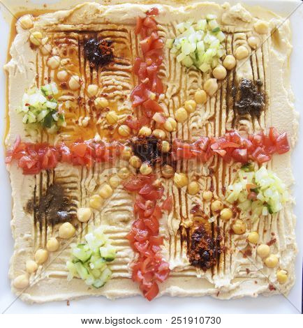 Hummus, A Levantine Dip Decorated With Chickpeas, Tomatoes, Cucumbers And Spices On A Square Plate,