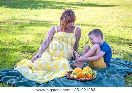 Beautiful Pregnant Caucasian Woman And Her Pre-school Age Son At The Picnic In The Public Park.