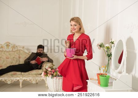 Planting Concept. Sensual Woman With Gardening Tool For Planting And Man Reading On Sofa. Planting A