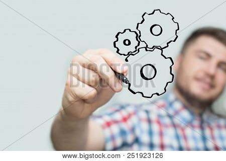 Man With Black Marker Draws On A Transparent Board Or Glass Wall. Gear Wheel Of Mechanism