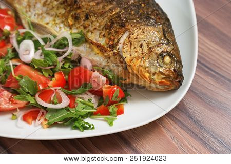 Fish Dish. Roasted Crucian Carp On White Plate With Fresh Mix Vegetable On Table. Close-up Fried Car
