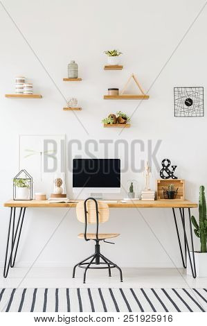 Wooden Shelves With Plants And Pots On A White Wall, Above An Industrial Desk With Modern Desktop Co