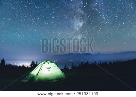 Green tent lighted from the inside by a flashlight against the backdrop of an incredible starry sky. Amazing night landscape. Tourism concept
