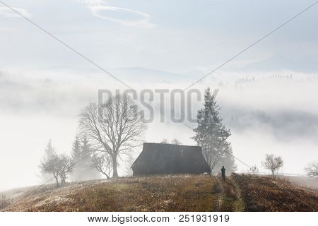 Mountain valley during sunrise. Alone house on autumn foggy meadow. Carpathian mountains, landscape photography