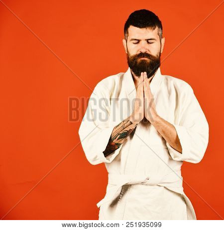 Karate man calm face image photo free trial bigstock man with beard in white kimono on red background combat master holds hands together in traditional greeting japanese martial arts concept m4hsunfo