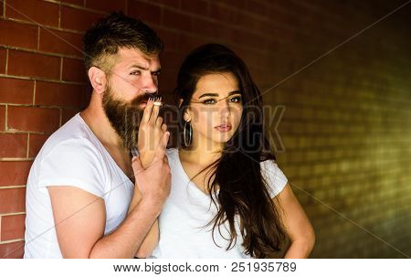 Couple In Love Hugs While Smoking Cigarette Brick Wall Background. Couple Find Place To Hide From Wi