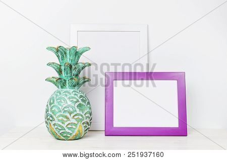 Wooden Empty Frames For A Photo And Wooden Emerald Pineapple On A Background Of A White Wall. Blank