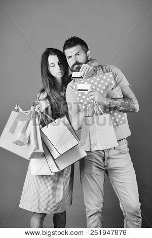 Couple In Love Holds Shopping Bags On Blue Background And Hugs. Shopping And Spending Concept. Guy W