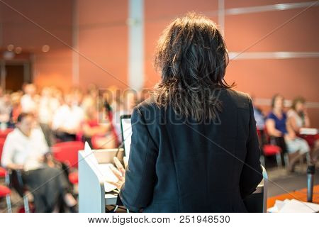 Female Speaker Giving A Talk On Corporate Business Conference. Unrecognizable People In Audience At