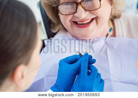 Dentist woman performing dental bleaching at senior patient showing possible outcomes