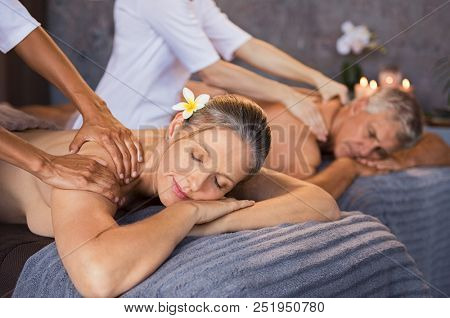 Senior couple in spa salon getting massage. Relaxed senior couple enjoying body treatment in a wellness center. Retired man and woman receiving a back massage from masseur in a spa salon.