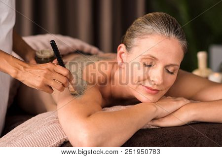 Relaxed mature woman enjoying a mud skin treatment at spa. Portrait of beautiful senior woman having clay body mask applyed by beautician in a wellness center. Exfoliation scrub beauty treatment.