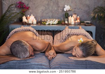Senior loving couple lying naked at spa center holding hands. Mature woman and man lying on massage table for a spa treatment. Beautiful relaxed couple enjoy the peace after a beauty treatment.