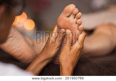 Closeup of masseuse doing foot reflexology to woman at spa. Therapist hands doing foot massage at wellness center. Woman receiving a feet massage at health spa.