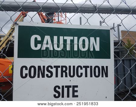 Caution Construction Site Sign On Metal Chain Link Fence