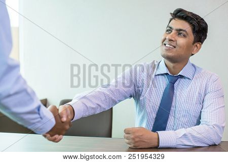 Indian Businessman Greeting Partner In Office. Business Leader And His Unrecognizable Partner Shakin
