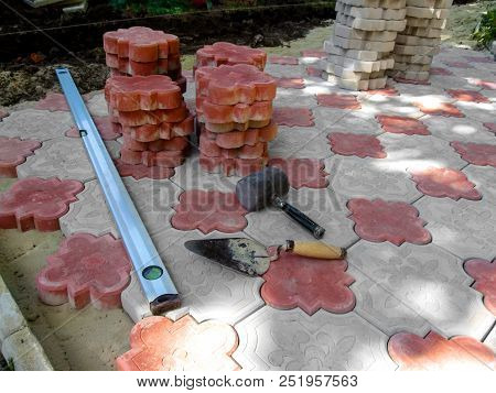 Work place for laying beautiful red and white figured paving slabs. Unfinished laying of paving slabs on the floor, a pile of red tiles, a building level tool, a trowel and a rubber mallet poster