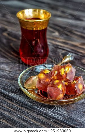 Turkish joys with different nuts is a glass of tea and a spoon. Eastern sweets. Traditional Turkish delight (Rahat lokum) on a wooden background. View from above . poster